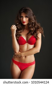 Pretty elegant lady in beautiful red lingerie against dark gray background