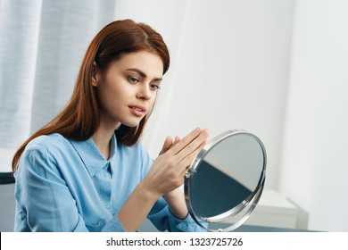 Pretty elegant woman in blue shirt looking in the mirror