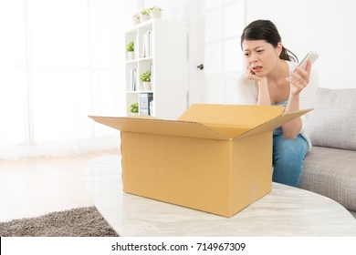 pretty elegant woman opening online shopping parcel box feeling sadness when she sitting on sofa using mobile smartphone relaxing at home.