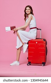 pretty elegant woman with a passport in her hands and tickets for a plane on a pink background red suitcase