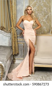 Pretty elegant woman wearing bright slit mermaid evening dress and standing in luxury interior near bed and armchair. Sexy stunning girl with long curly blonde hair.