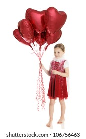 A pretty elementary girl in red and loaded up with a white boa, strands of hearts and a big bouquet of red, heart-shaped balloons.  On a white background.