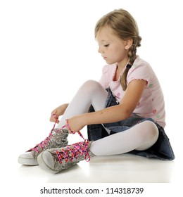 A pretty elementary girl tying heart-covered, neon pink laces on oversized sparkly high-top sneakers.  On a white background.
