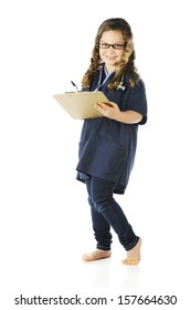 "A pretty elementary ""nurse"" wearing scrubs and glasses looking at the viewer as she writes on her clipboard."