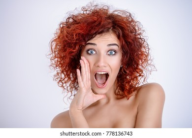 Pretty emotional girl with curly foxy hair shouts, putting his hand to his mouth. Beauty cosmetics and hair concept. White background. Copy space.