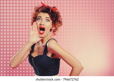Pretty emotional girl with curly foxy hair shouts, putting his hand to his mouth. Pin-up style.