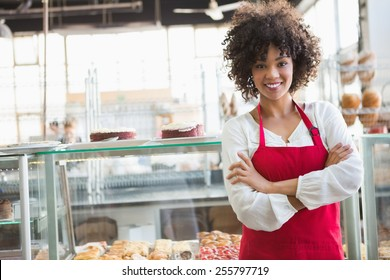 Pretty employee posing with arms crossed at the bakery
