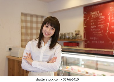 Pretty employee posing with arms crossed at a cafe