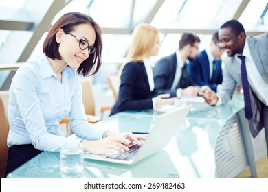Pretty employee typing on laptop in working environment