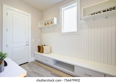 Pretty entrance foyer with a wall clad in board and batten lined with an extra long built-in bench with storage drawers topped with white and brown pillows. Northwest, USA