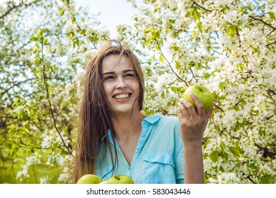 Pretty in establishment of branches of a blossoming apple. Portrait of face young beautiful woman holding apple on Spring blooming apple tree background summer nature. spring season