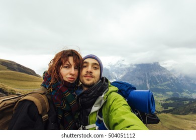 Pretty, european, couple standing on the trek in the mountains.Switzerland.
