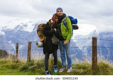 Pretty, european, couple standing on the trail in the mountains. Switzerland.