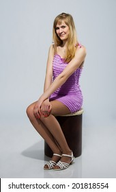 Pretty european girl is smiling and sitting on light background wearing violet pink purple short dress