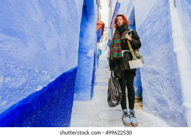 Pretty, european red haired girl standing  on the narrow street of blue city in Morocco. (Chefchaouen/ Chaouen)