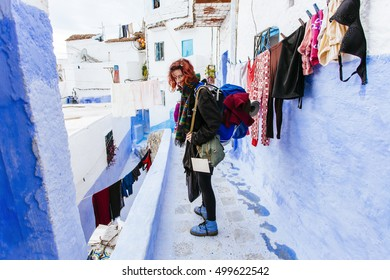 Pretty, european red haired girl standing on the pavement in blue city, around her laundry is hanging on the line. (Chefchaouen / Chaouen, Morocco)