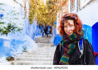 Pretty, european red haired girl standing on the narrow path of blue city in autumn time. Morocco, the blue town. (Chefchaouen / Chaouen)