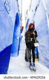 Pretty, european red haired girl standing on the narrow path of blue city. Morocco.  (Chefchaouen / Chaouen)