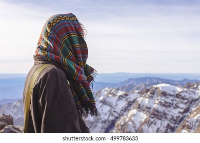 Pretty, european red haired girl with the ethnic patterned hood on her head standing on the top of Tubkal mountain and looking at the distant Atlas peaks, Morocco.