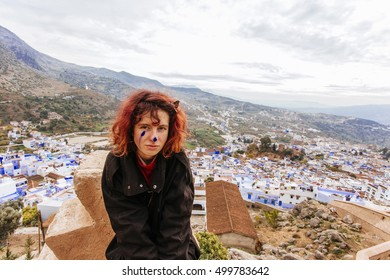 Pretty, european red haired girl standing and looking forward, with the blue painted buildings on the background. Morocco. (Chefchaouen / Chaouen)