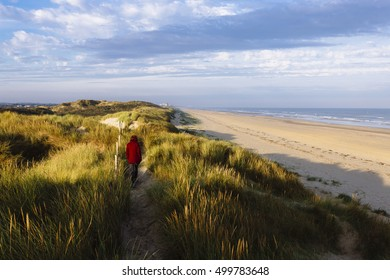 Pretty, european red haired girl waling on the sand dunes and grass growing next to the beach in de Panne, Belgium.