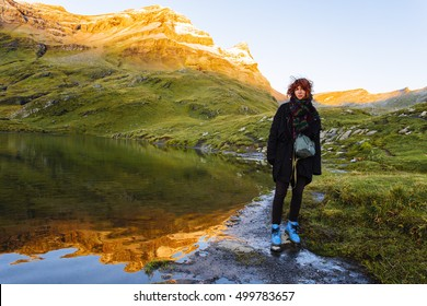 Pretty, european red haired girl standing on the stone at the lake reflecting the distant mountain and looking straight ahead of her. Switzerland