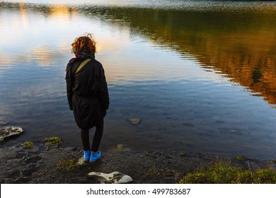 Pretty, european red haired girl standing on the stone and looking at the lake reflecting the distant mountain.  Switzerland.