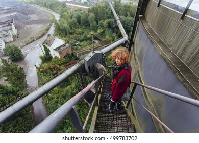 Pretty, european red haired girl standing on the stairs of the abandoned power plant, high upper ground, turning her head and looking straight at the viewer. Belgium.