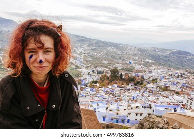 Pretty, european red haired girl standing  and looking forward, on the background of the blue painted buildings. Morocco. (Chefchaouen / Chaouen)