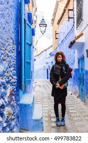 Pretty, european red haired girl standing  and looking forward, surrounded by blue painted buildings. Morocco. (Chefchaouen / Chaouen)