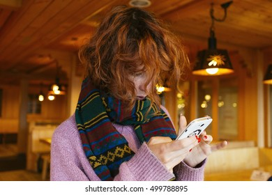 Pretty, european red haired girl standing  and using her phone in the wooden interior full of warm light, Switzerland