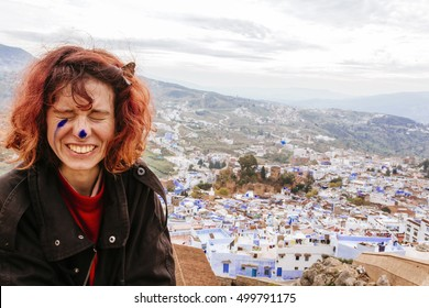 Pretty, european red haired girl sitting with the panorama of the blue city in the background. Morocco (Chefchaouen / Chaouen)