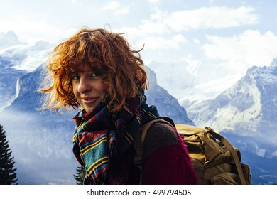 Pretty, european, red haired girl smiling, with the mountains in the background. Switzerland.