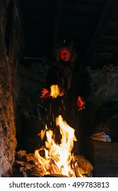 Pretty, european, red haired witch practicing witchcraft by forming a fire ball in the cottage house. Switzerland.
