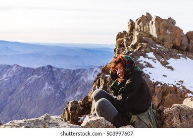 Pretty, european, red-haired girl sitting on the stone on the top of the mountains. Toubkal, Atlas mountains, Morocco.