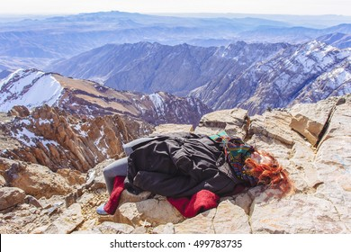 Pretty, european, red-haired girl sleeping on the top of Tubkal mountain exhausted after climbing through the ice and stones. Panorama of Atlas Mountains in the background. Morocco.