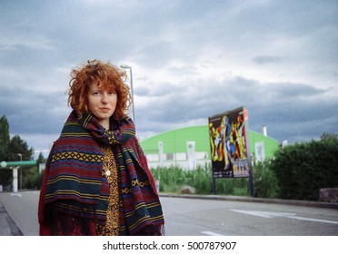 Pretty, european, red-haired girl standing on the street in the city in the cloudy weather. Germany. (photograph taken on the film)