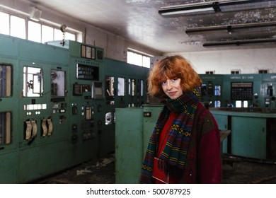 Pretty, european, red-haired girl standing in the abandoned power plant. Charleroi, Belgium.