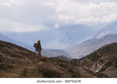 Pretty, european, red-haired girl wearing her backpack on her back stopping and turning back on the trail in the mountains. Annapurna Circuit, Himalayas, Nepal.