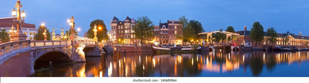 Pretty evening illuminations of the historic and richly decorated Blauwbrug (1883) bridge in Amsterdam. Skinny bridge and Stopera music theatre visible. Stitched panoramic image.