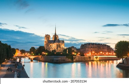 Pretty evening illuminations of the stunning Notre-Dame Cathedral (1163) and parisian apartments along the banks of the river Siene, Paris.