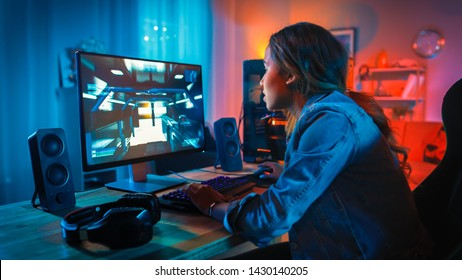 Pretty and Excited Black Gamer Girl Has a Tense Moment in Her First-Person Online Shooter Video Game on Her Computer. Room and PC have Colorful Neon Led Lights. Cozy Evening at Home.