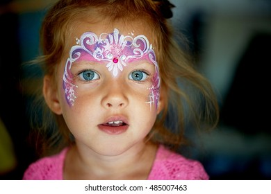 Pretty exciting blue-eyed girl of 2 years with a face painting