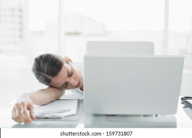 Pretty exhausted businesswoman sitting at her desk sleeping in her office