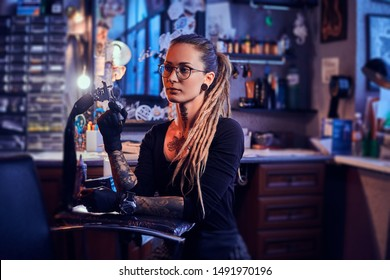 Pretty expirienced tattoo artist in glasses is tuning her new tattoo machine before tattooing session.