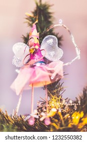 Pretty fairy angel decoration hanging from the top of a Christmas tree. She has sparkly net wings and is wearing a crown. There are fairy lights around her