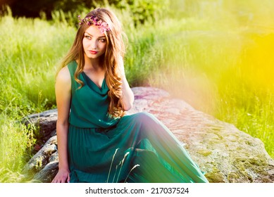 pretty fairy: young woman cute brunette girl sitting on stone in green dress with pink wreath of flowers & sun light flares of rays & looking at camera on summer outdoor copy space background