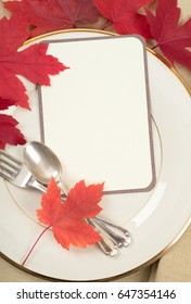 Pretty Fall Place Setting with fork, spoon, maple leaves and a cream white invitation card on a china plate.  A flat lay vertical orientation with blank room or space for your text, copy or words.