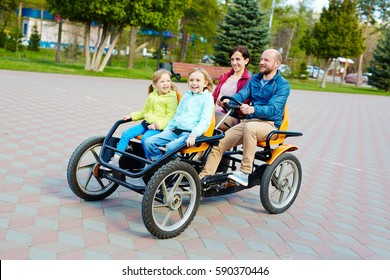 Pretty family having fun in spring park: bearded middle-aged father driving orange quadricycle pedal car while his joyful family sitting in it with wide smiles