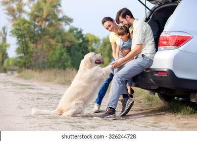 Pretty family is resting in forest and playing with dog. They are sitting on open car boot and embracing. The man and woman with girl are smiling. Copy space in left side